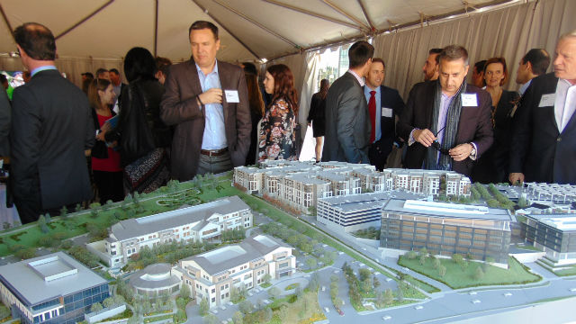 Guests at the groundbreaking view a model of the development. Photo by Chris Jennewein