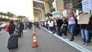 Arriving passengers at Lindbergh Field walk a distance from protesters to get to their cars. Photo by Chris Stone