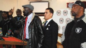 The Rev. Shane Harris of the National Action Network stands behind Richard Olango, father of slain Alfred Olango. Eddie Price of the NAACP is at right. Photo by Ken Stone