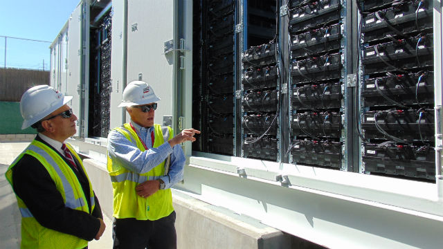 Escondido Mayor Sam Abed (left) listens as an SDG&E employee describes the battery system.