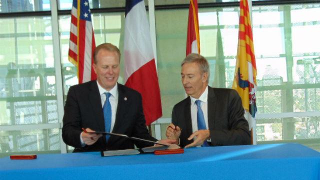 Mayor Kevin Faulconer (left) and Bernard Deflesselles sign the memorandum of understanding. Photo by Chris Jennewein