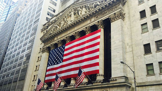 An American flag hanging from the New York Stock Exchange building. Photo via Wikimedia Commons