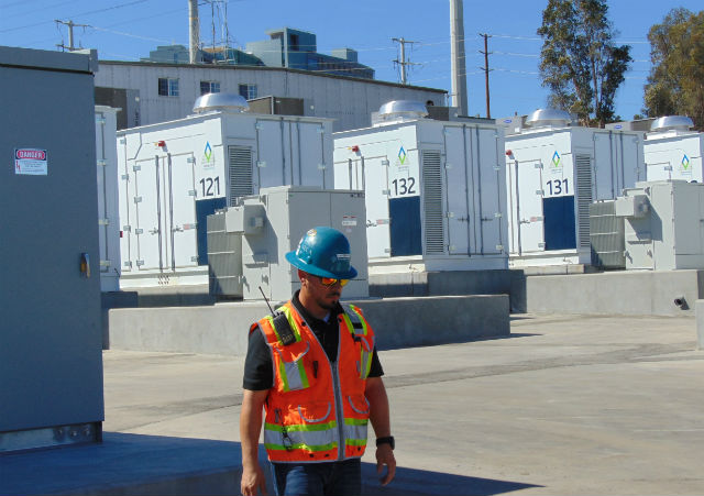 An SDG&E employee walks in front of four of the battery units. Photo by Chris Jennewein