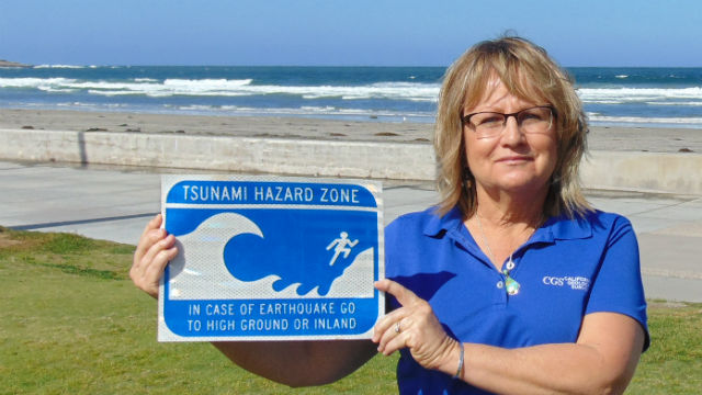 Cynthia Pridmore of the California Geological Survey holds a tsunami warning sign at La Jolla Shores Beach. Photo by Chris Jennewein