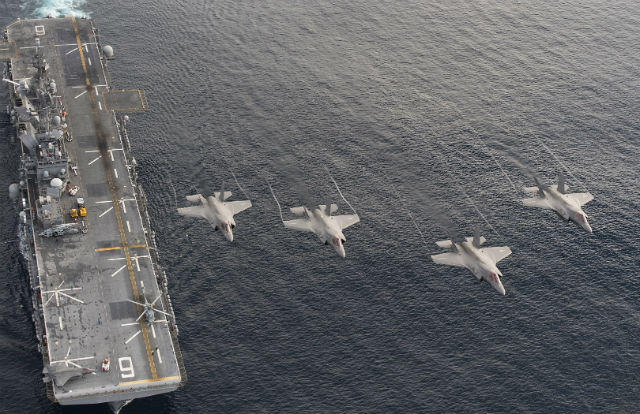 Marine Corps F-35 Lightning II fighters fly alongside the USS America in