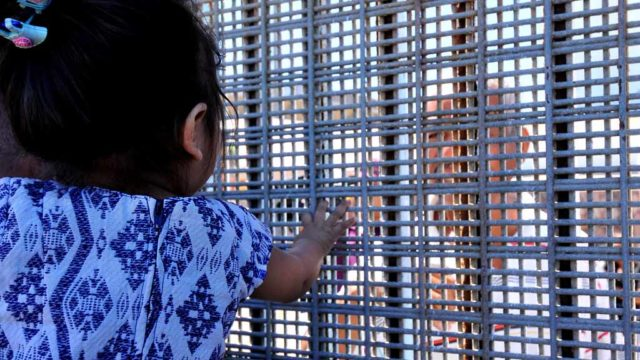 A toddler on the U.S. side of the border visits with a relative on the other side