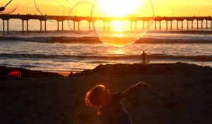 A young boy at Ocean Beach pier tries to pop a bubble. Photo by Chris Stone