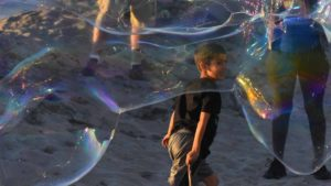 A young boy enjoys chasing the bubbles near Ocean Beach Pier. Photo by Chris Stone