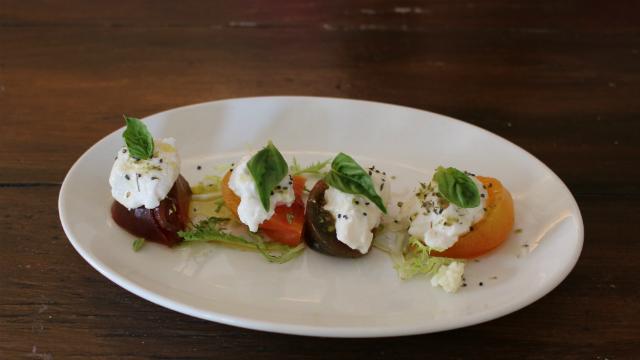 Organic heirloom tomato covered with rice mozzarella in 'Caprese Mozzarella' a gluten-free dish. Photo by Cassia Pollock.