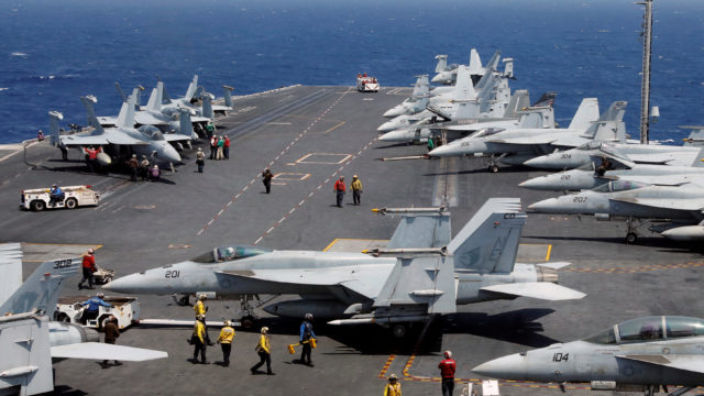 Navy personnel prepare to launch an F-18 fighter from the USS Carl Vinson during an exercise in South China Sea. REUTERS/Erik De Castro