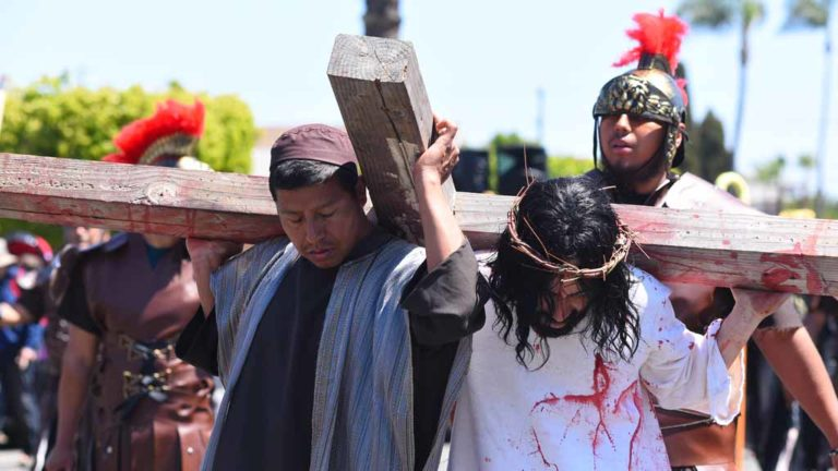 Actors portraying Simon of Cyrene and Jesus carry the wooden cross through a neighborhood adjacent to Our Lady of Guadalupe Church. Photo by Chris Stone