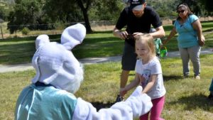 Mackenzie of Lakeside, pleased to meet the Easter Bunny, gave him a hug at El Monte County Park in Lakeside. Photo by Chris Stone