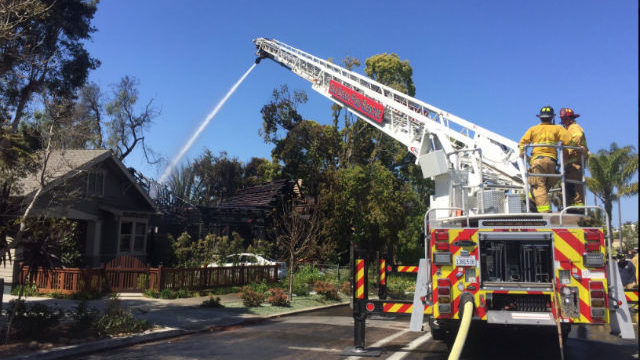 San Diego firefighters pour water on the charred home in Mission Hills. Courtesy San Diego Fire-Rescue