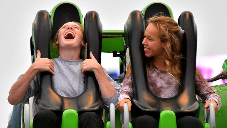 Two girls laugh during a ride in the Fun Zone at the 2017 San Diego County Fair.