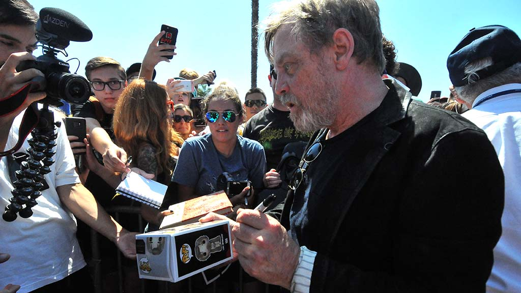 Mark Hamill signs autographs for cheering fans.