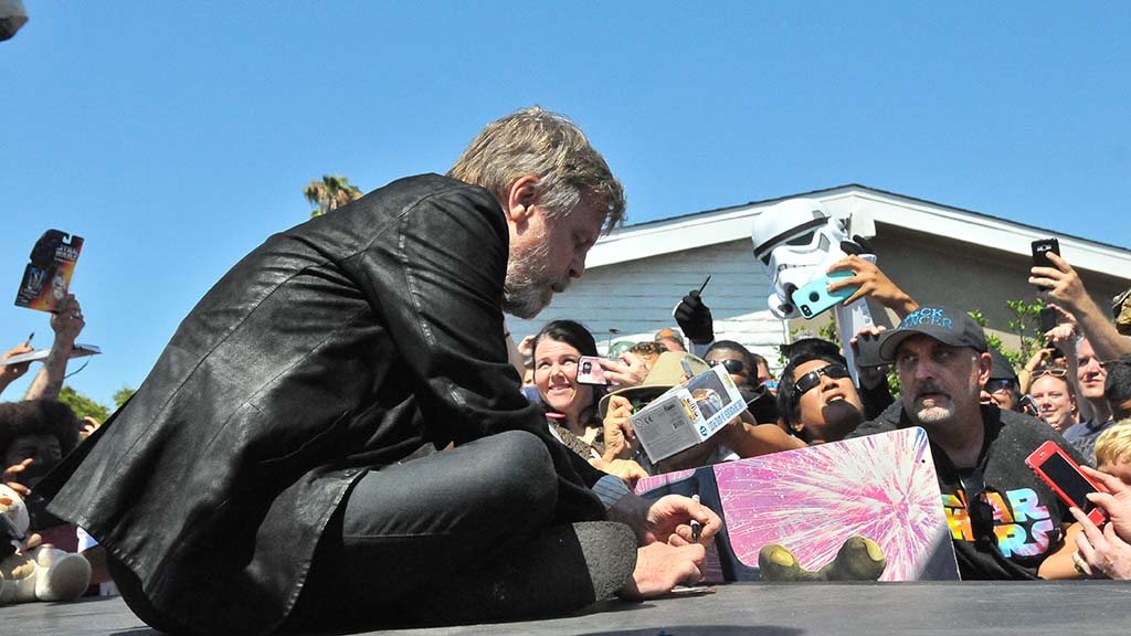 Actor Mark Hamill signs autographs for fans after the street unveiling.