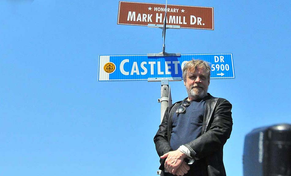 Mark Hamill stands by the honorary sign on a street where he lived as a child.