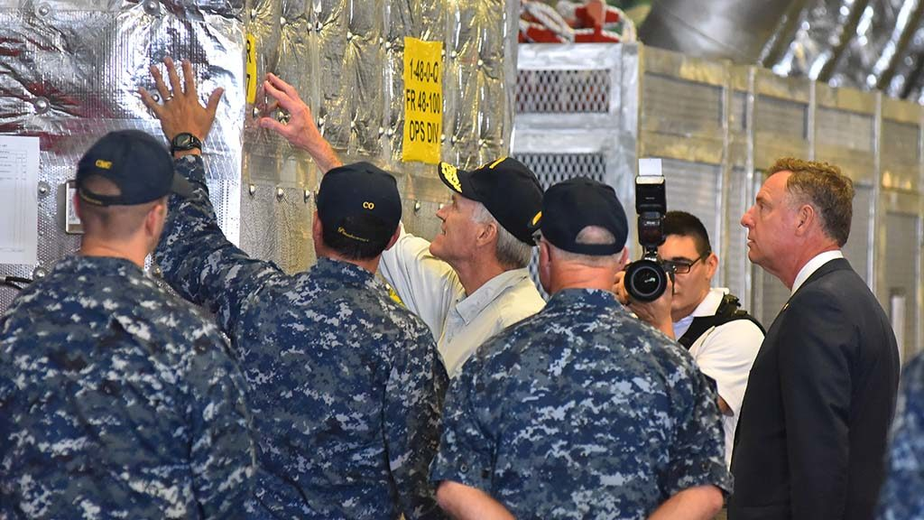 USS Gabrielle Giffords Cmdr. Kevin P. Meehan points out the insulation of the ship to Navy Secretary Richard Spencer.