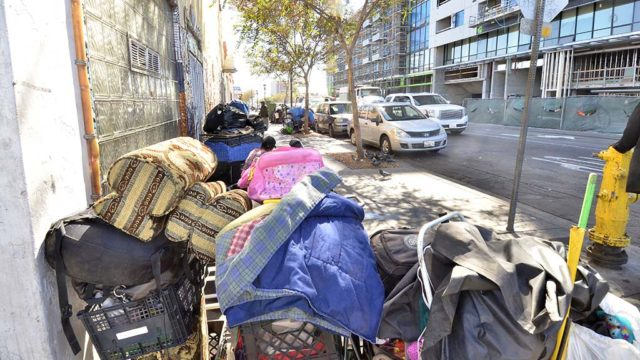 Shopping carts filled with belongings of homeless people line a street in downtown San Diego.