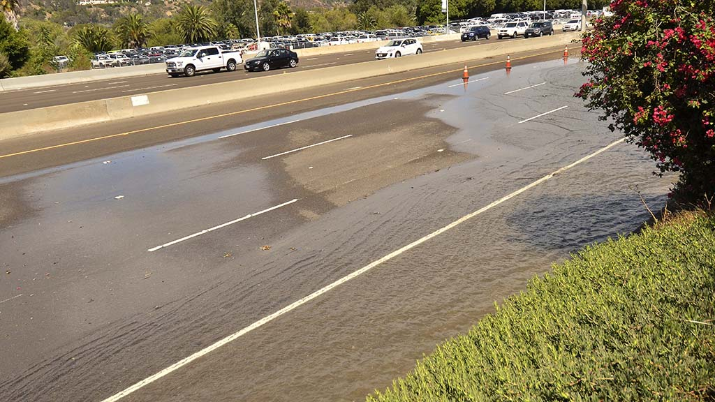 Water flows from a water main break on eastbound Interstate 8.
