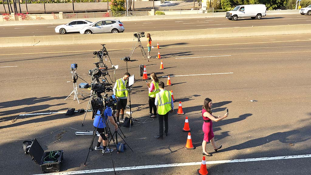 Television crews prepare for broadcast in the middle of eastbound Interstate 8