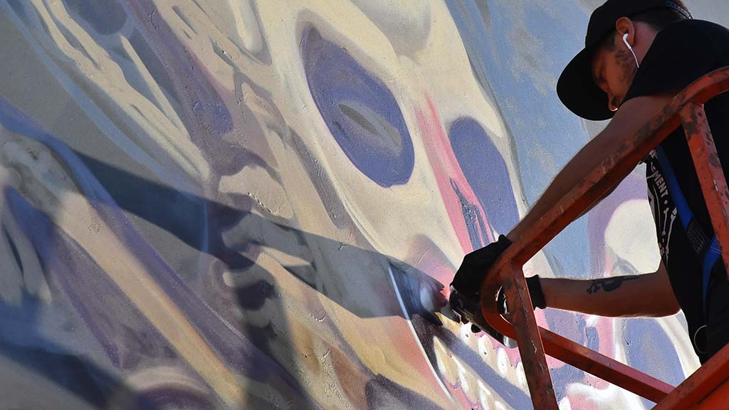 An artist puts finishing touches on a painting at KAABOO Del Mar.