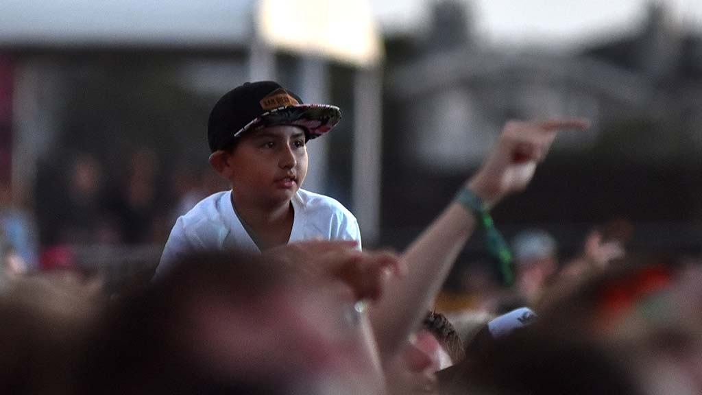 A young boy on someone's shoulder watches the Ice Cub performance at KAABOO Del Mar.