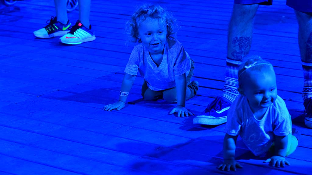 A toddler and baby bathed in blue light play at KAABOO.