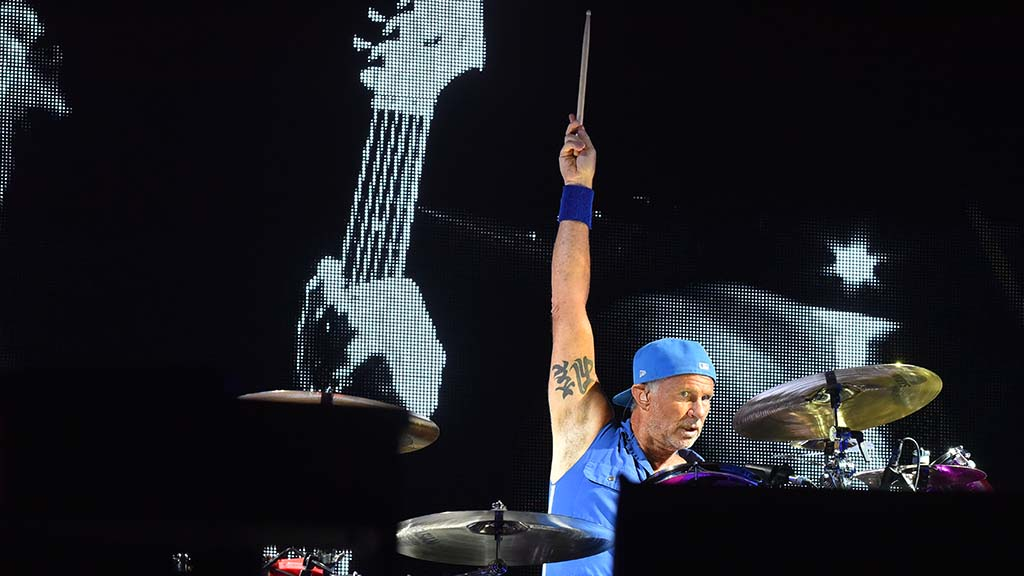 Chad Smith, drummer for Red Hot Chili Peppers, signals to the crowd.