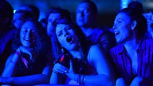 Fans bathed in blue light sing along to songs played by Red Hot Chili Peppers