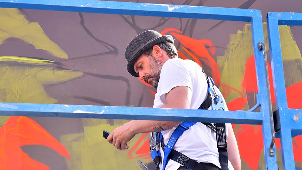 Case Maclaim of Germany works on his 20 foot by 30 foot mural at KAABOO Del Mar