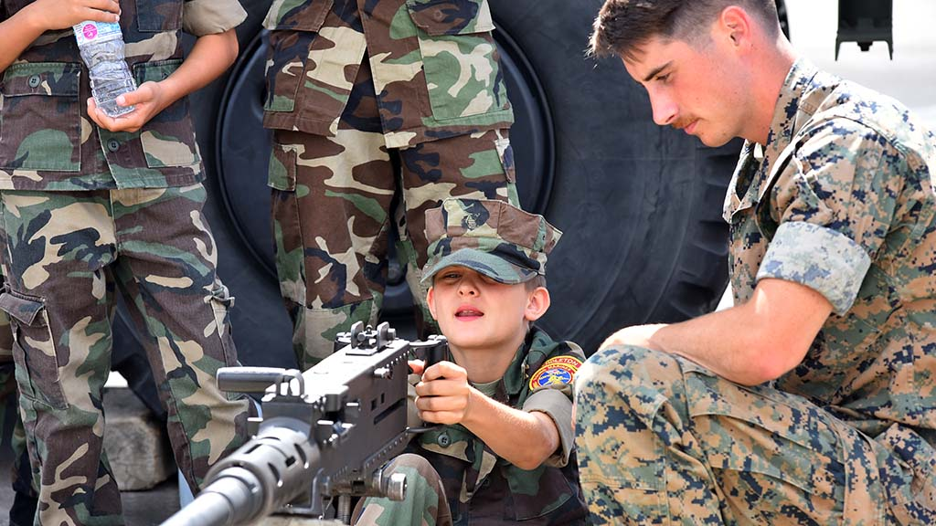 A child dressed in military fatigues looks at a weapon.