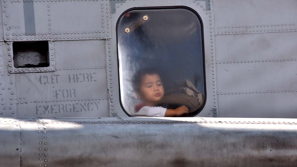 A child look out from an airplane window at the 2017 Miramar Air Show.