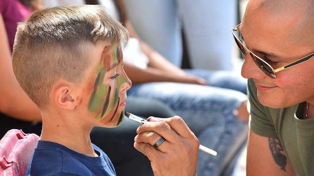 Eli, 7, gets his face painted by Gunnery Sgt. Armando Pabon.