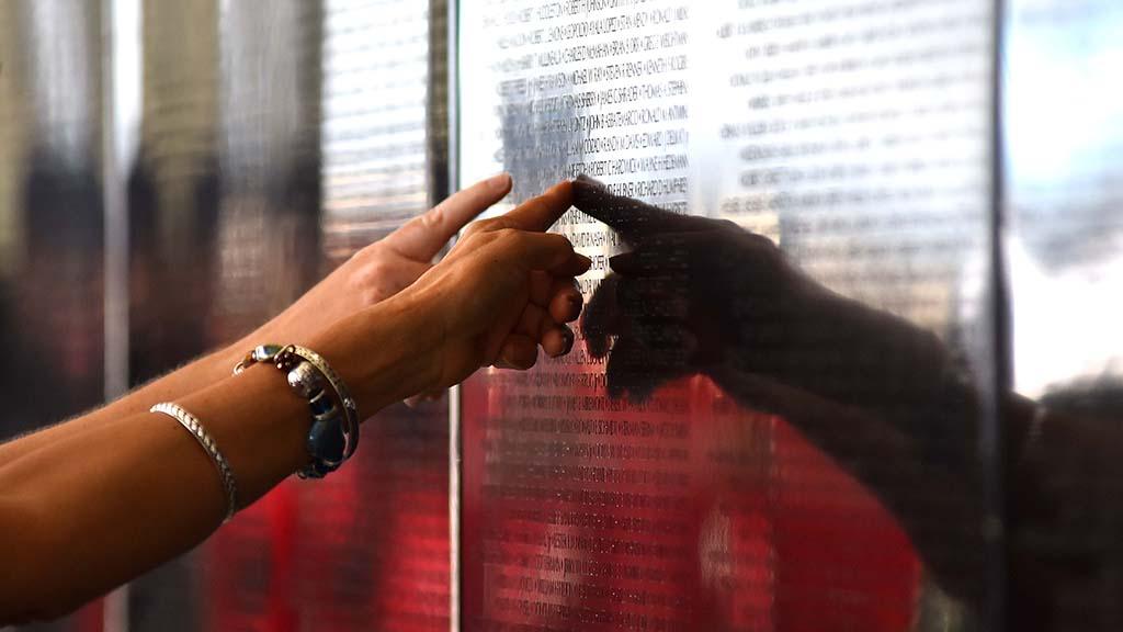 Women identify a name of a fallen soldier in the Vietnam War.