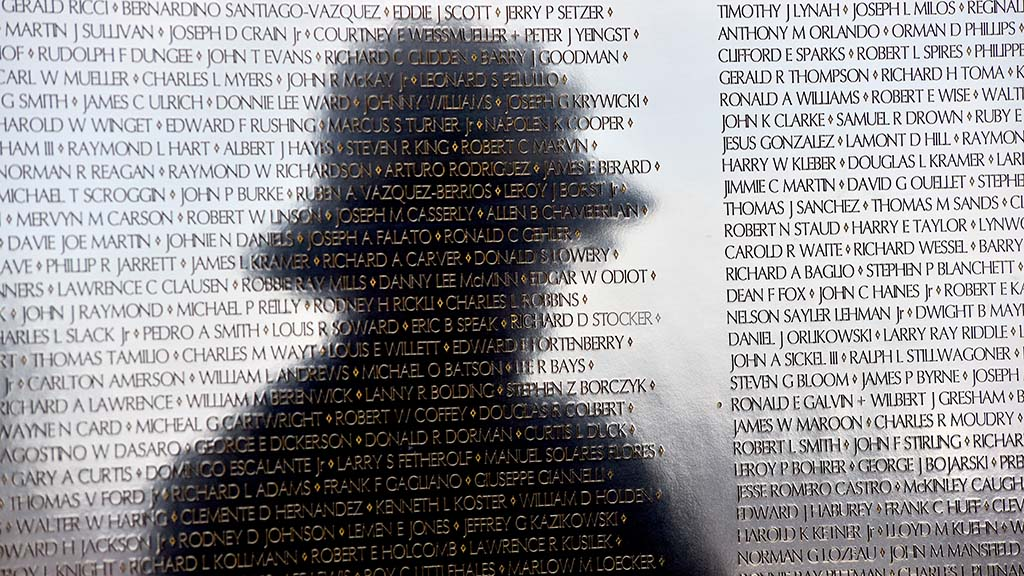 A veteran pauses to look at the names of the mobile Vietnam Memorial Wall