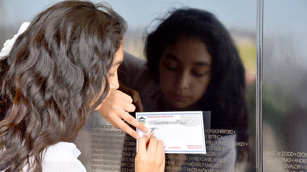 A girl makes a rubbing of a name at the mobile Vietnam Memorial Wall