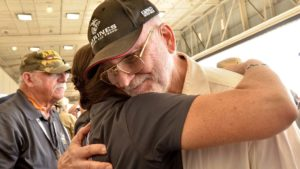 A Vietnam War vet gets a welcome hug from Stacia Nemeth with the mobile wall.