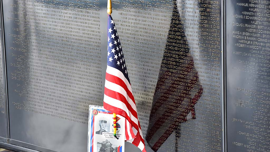 Family members left photos of their lost loved ones at the Vietnam Memorial Wall.