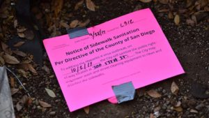 A city notice in a tree well notifies the homeless of upcoming power washing.