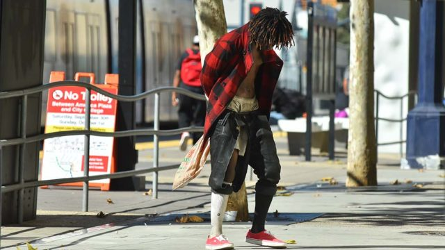 A homeless man dances on a sidewalk in downtown San Diego.
