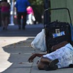 A homeless woman sleeps on the sidewalk in downtown San Diego.