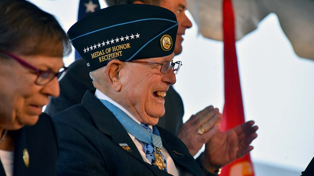 "Medal of Honor recipient Hershel ""Woody"" Williams smiles as the crowd applauds."