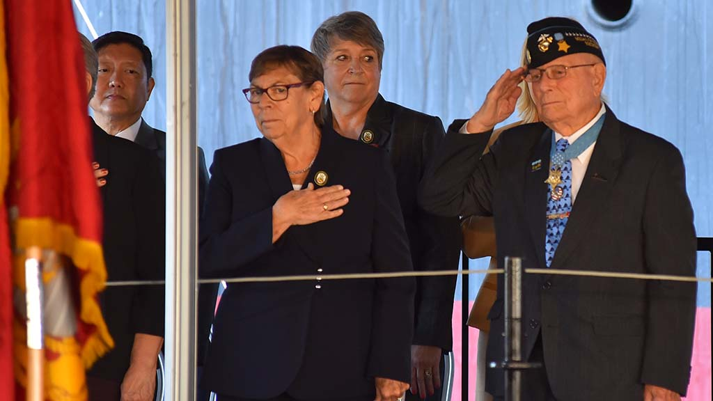 "Medal of Honor recipient Hershel ""Woody"" Williams salutes as a Marine Corp flag."