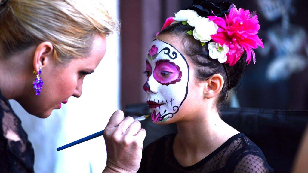 A young girl was one of many adults and children who had their faces painted for Dia de los Muertos.