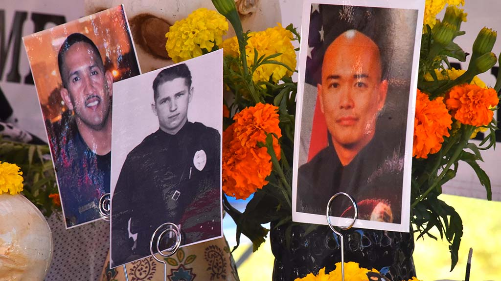 Fallen Officer J.D. deGuzman's photo (right) was among those in an altar to those who died in the line of duty.