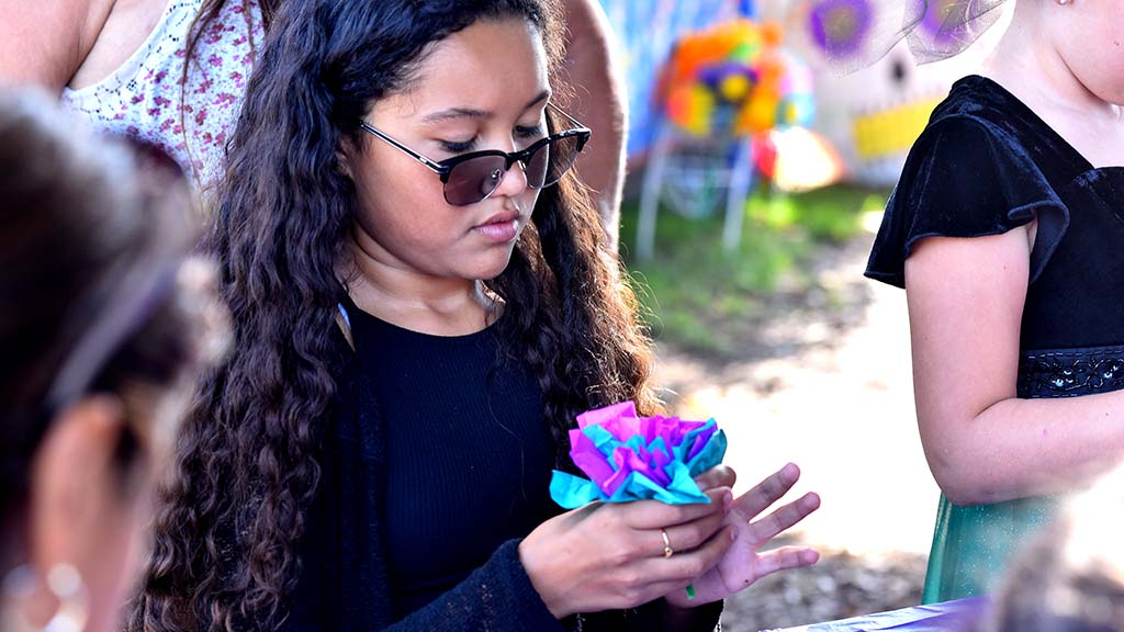 A young girl learns how to make paper flowers in Old Town.