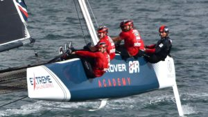 Sailors lean out to counterweight the boat during a race.