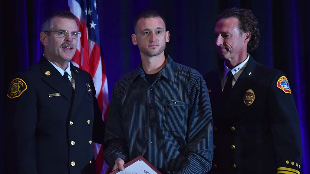 San Diego Fire Chief Brian Fennessy (left) honors Chris Struble (center) for saving a woman's life