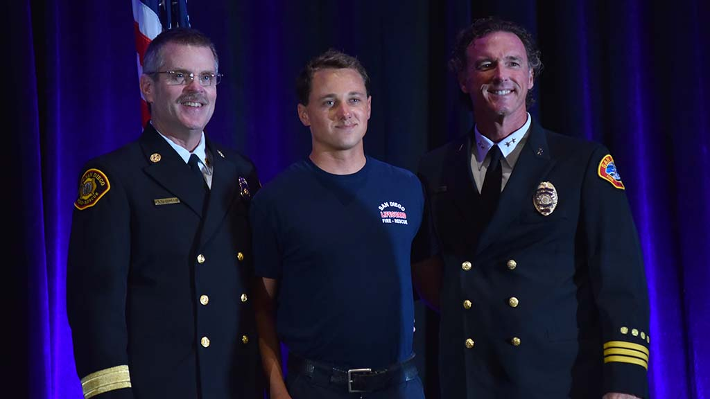 San Diego Fire Chief Brian Fennessy (left) poses with Trevor Wageman (center), the 2017 Lifeguard I of the Year.